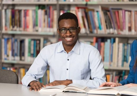 Portrait Of Clever Black Student With Open Book Reading It In College Library - Shallow Depth Of Field