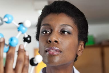 African American female teacher looking at molecular structure in science lab